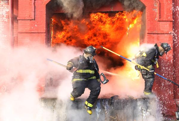 St. Louis firefighters jump from a loading dock to escape flames at a warehouse in downtown St. Louis on December 16, 2013.