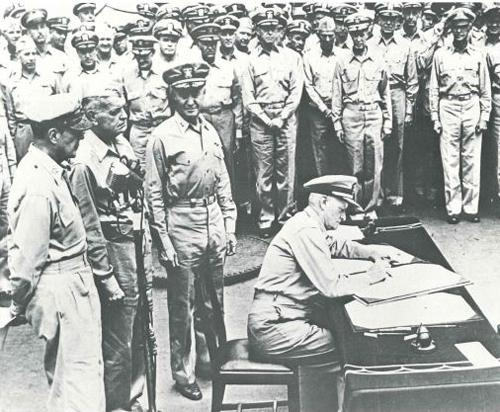 "Caption reads: ""Fleet Admiral Chester Nimitz signs the Intrument of Formal Surrender during the ceremony on Missouri."""