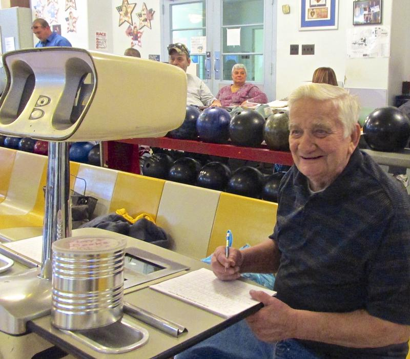 Volunteer Don Hammer keeps score. The bowling alley has pinsetting equipment that dates to the 1960s and no automatic scoring machines.