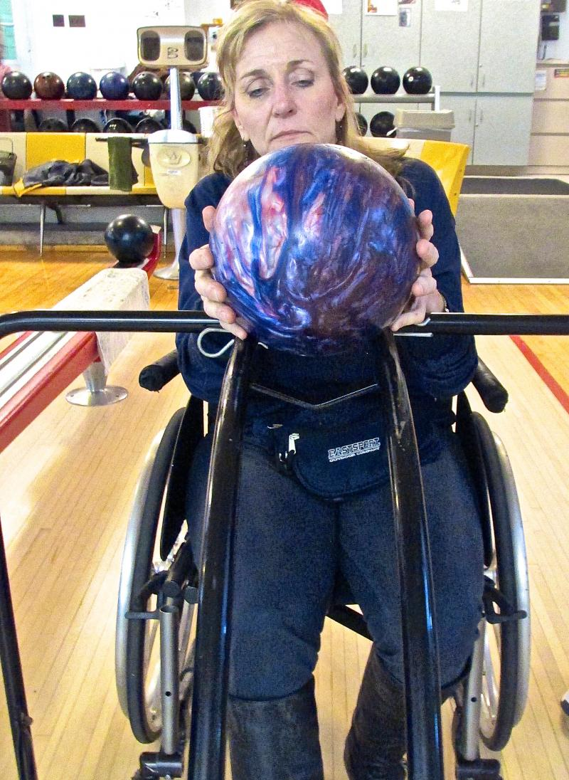 Veteran Ruth Kult bowls while seated in her wheelchair. The vets say it takes practice to learn how to bowl with the adaptive equipment.
