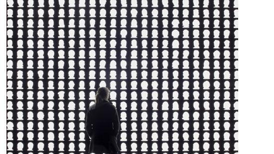 Alfredo Jaar, The Geometry of Conscience, 2010. A woman standing before silhouettes of heads.