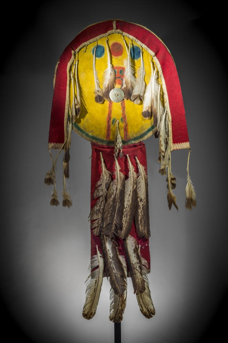 Wazhazhe (Osage), Shield, hide, feathers, cloth, metal and pigment, 18.5 x 44 inches, collection of Osage Tribal Museum