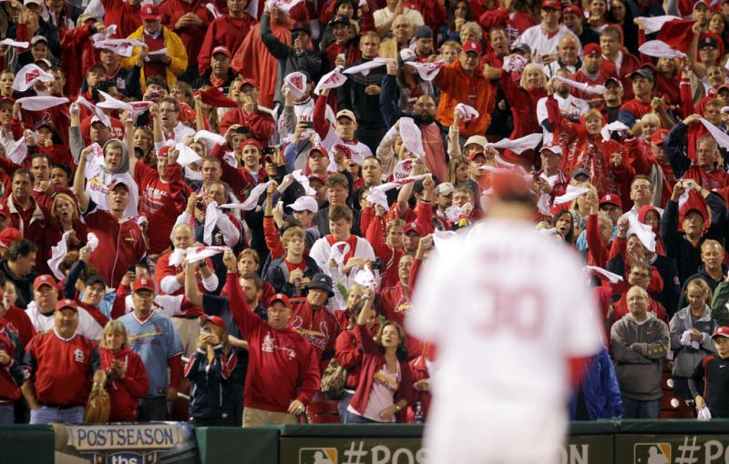 Fans wave their rally towels as St. Louis Cardinals pitcher Jason Motte delivers a pitch in the ninth inning against the Milwaukee Brewers in Game 3 in the NLCS at Busch Stadium in St. Louis on October 12, 2011.  St. Louis won the game 4-3.