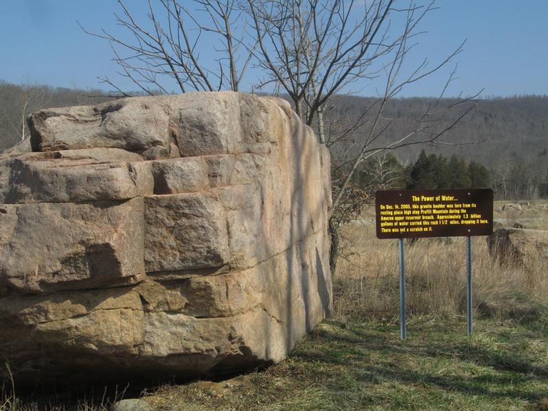 The sign says: On Dec. 14, 2005, this granite boulder was torn from its resting place high atop Proffit Mountain during the Ameren upper reservoir breach. Approximately 1.3 billion gallons of water carried this rock 1 1/2 miles, dropping it here.