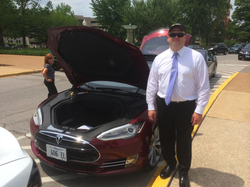 A Tesla owner from Illinois stands next to his vehicle at the state Capitol in 2014 as lawmakers were debating a measure that would have required the company to set up franchises.