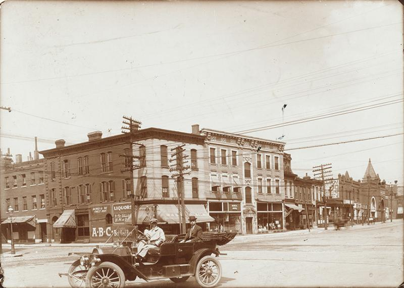 1911: A chauffeur-driven automobile waits on the north side of the 3300 block of Olive Street between Channing (Josephine Baker Boulevard) and Leonard Avenue. The buildings housed  a saloon and a store that sold medical books and instruments.