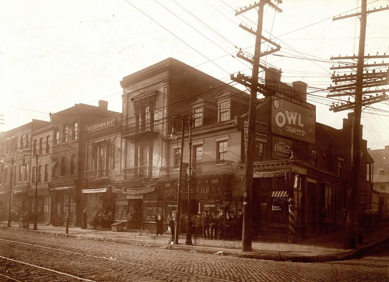 1911: George's barber shop and Fienup's Drugstore on the southwest corner of Broadway and Park. During warm weather, the area in Soulard resembled an outdoor market because merchants sold wares from sidewalk displays.