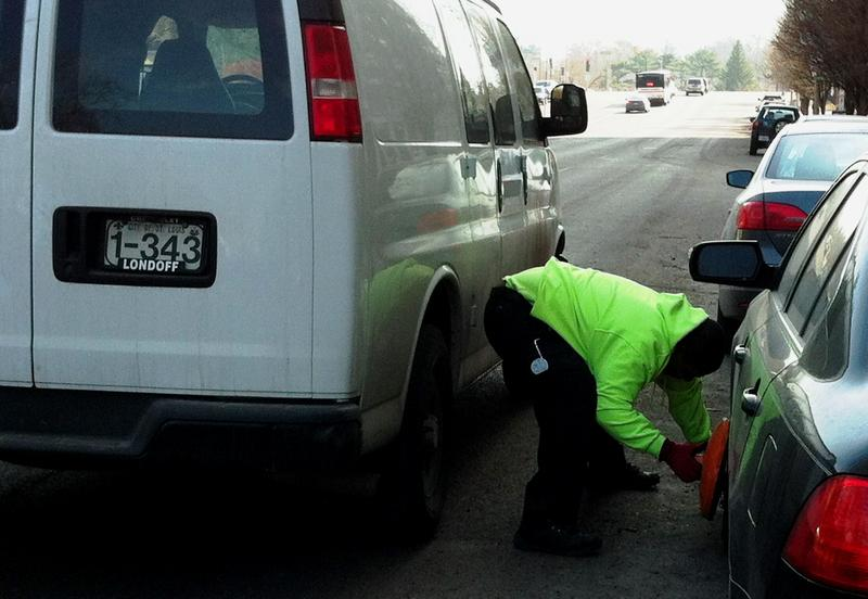 A city worker places a parking boot on the wheel of a vehicle on Union Blvd. in the Central West End.