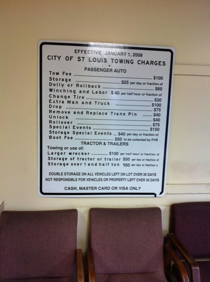 A sign in the lobby of the city impound displays how quickly fines and fees can add up for towed vehicles.