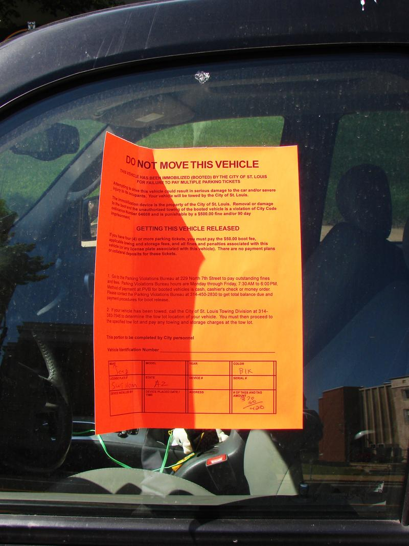 An adhesive notice is posted on the window of booted vehicle. The city of St. Louis can boot vehicles that have four or more late parking tickets.