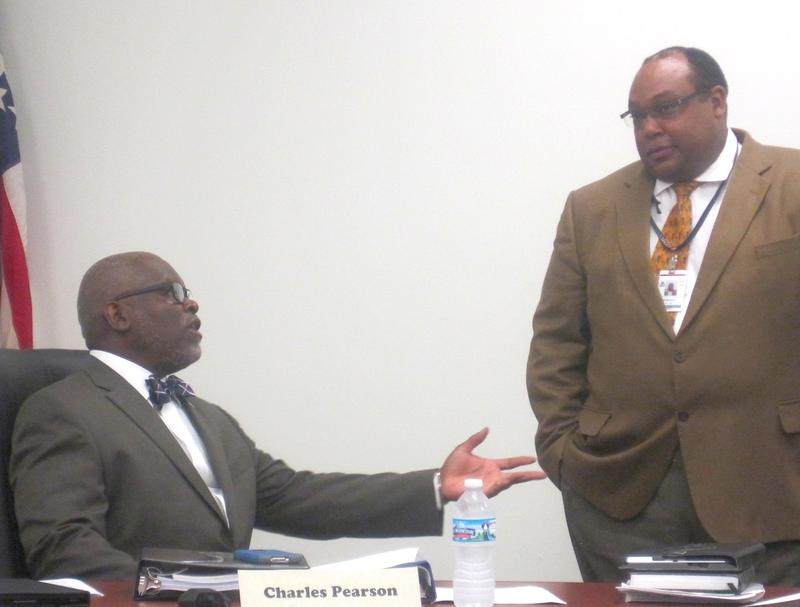 Charles Pearson, seated, talks with Superintendent Ty McNichols.