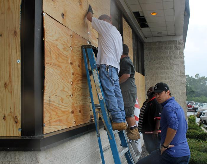 Volunteers board up the windows of Sam's Meat Market on Saturday, August 16, 2014.