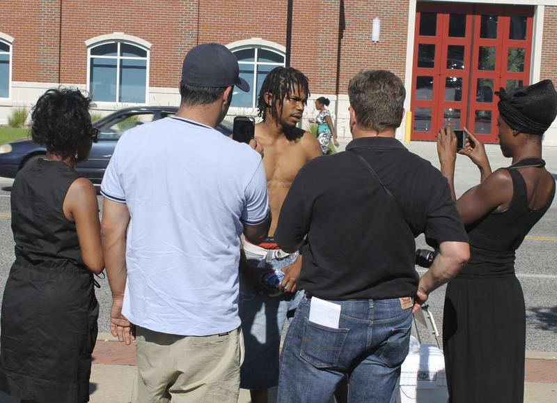 People gather to hear a man describe his experience with police. He declined to give his name.