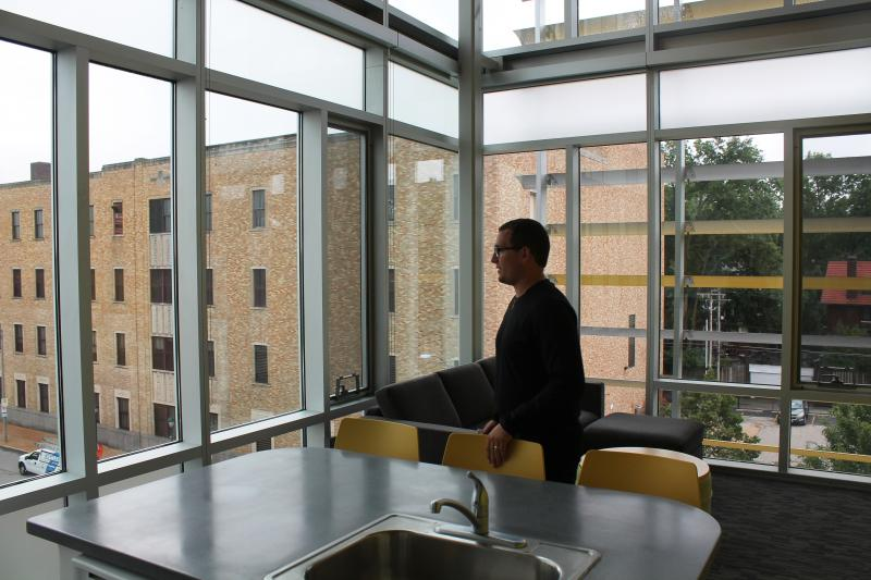 Tyler De Shon, a residential community director for Washington University, stands inside one of the dorm's three-bedroom apartments. The two-story flat has a big view of the Delmar Loop.