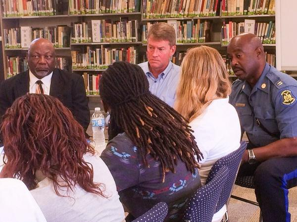 Missouri Attorney General Chris Koster, center, with Highway Patrol Capt. Ron Johnson, right, at area high school during height of unrest in Ferguson.