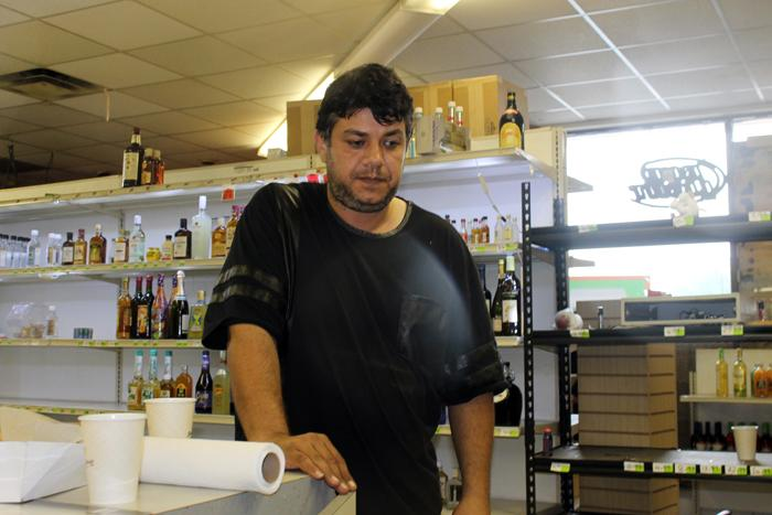Mike Jacoub, owner of Sam's Meat Market, stands behind the counter of his twice-looted store on Saturday, August 16, 2014.