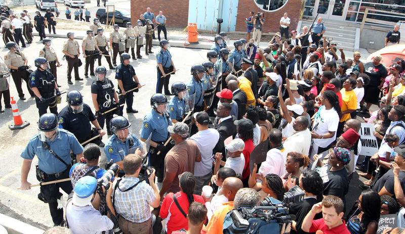 Protesters are greeted by lines of State and County police during a demonstration march on the Ferguson police station in Ferguson, Missouri on August 11, 2014. People are upset because of the Ferguson Police shooting and death of an unarmed black teenage