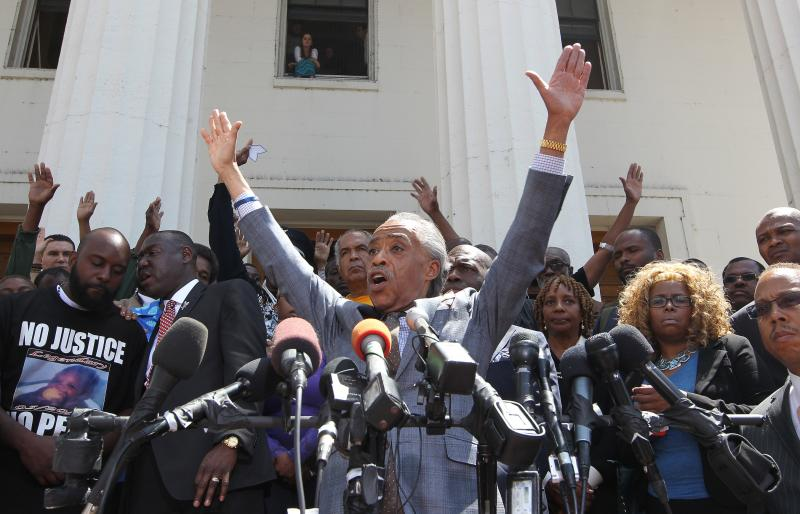"The Rev. Al Sharpton told a crowd gathered at the Old Courthouse, ""If you're angry, throw your arms up. If you want justice, throw your arms up."""