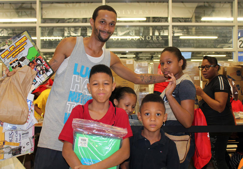 The Johnson-Mitchell family pose for a picture with their new school supplies on Saturday, August 2, 2014.