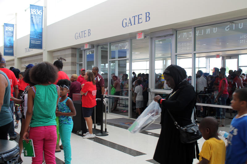 Groups of people are assigned a letter of the alphabet, then wait in the stands for their turn to pick up supplies.