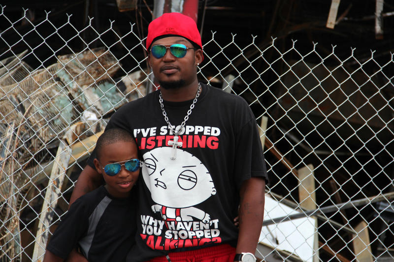 Darrell Bryant Senior and his son, Darrell junior, stand outside the burnt out remains of the QuikTrip on West Florissant Road in Ferguson.