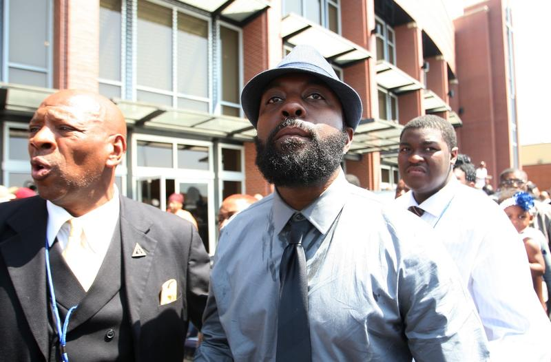 Michael Brown Sr., center, arrives at his son's funeral.