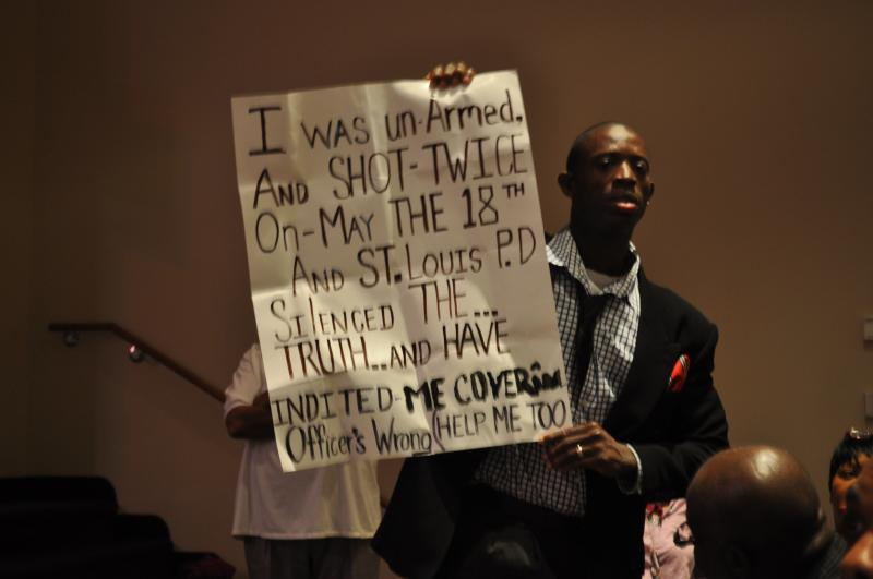 Michael Jackson holds up a sign during a tense moment during the Ferguson City Council meeting.