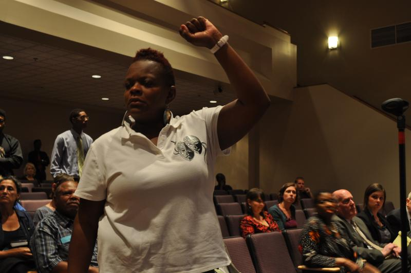 A speaker raises her fist during the public comment section of last night's Ferguson City Council meeting.