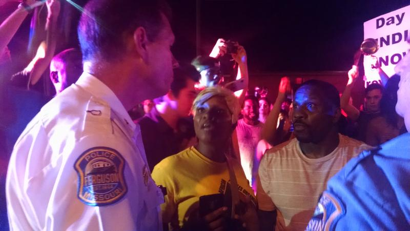 Ferguson Police Lt. Craig Rettke is confronted by two protestors in the middle of S. Florissant Road Sunday night.