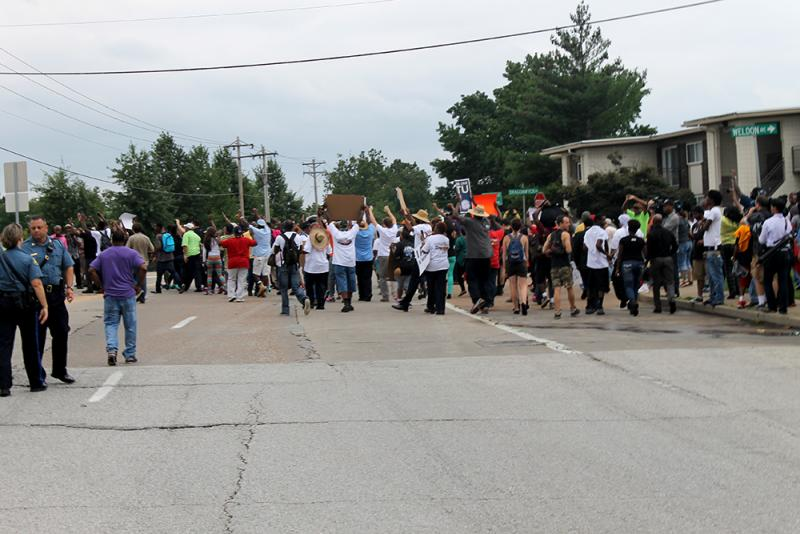 The crowd of protesters take a single lap around the median on Hanley Road before returning to the roadside.