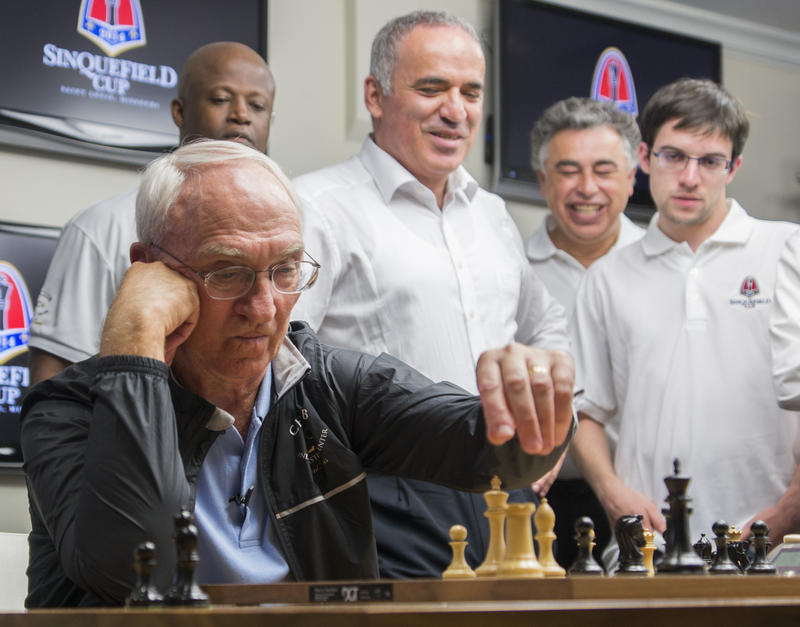 Rex Sinquefield prepares to make a move as Grandmasters look on. Behind, from left, are commentator Maurice Ashley, Garry Kasparov, Yasser Seirawan and Maxime Vachier-Lagrave.