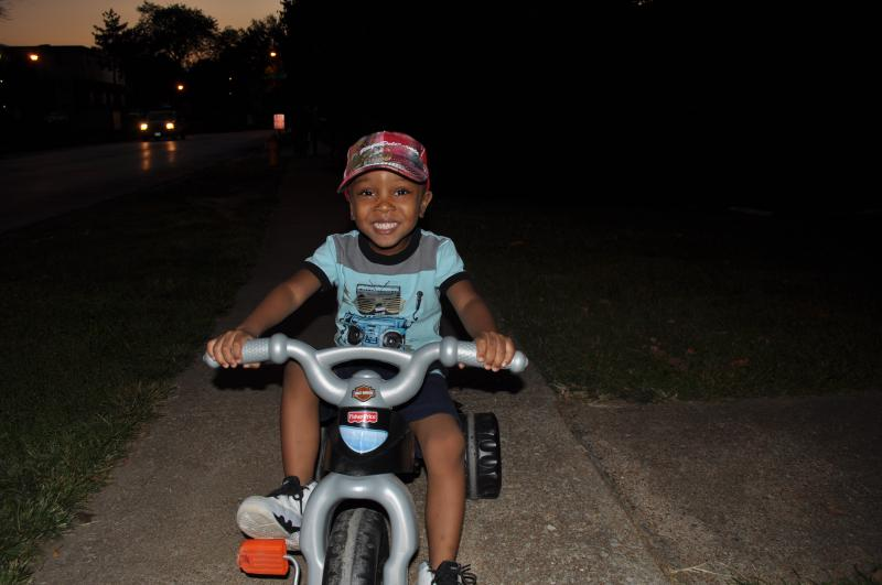 3-year-old Charles rides his tricyle near the Canfield Green Apartments.