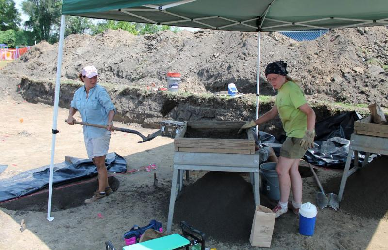 ISAS historic archaeologist Claire Dappert tosses shovels of dirt into a metal screen that archeology specialist Martha Mahich sifts through to look for any small artifacts that may have been missed.