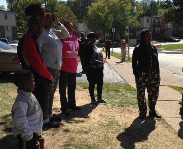 Christianna Jennings (far right) stands with neighbors next to the memorial for Michael Brown, next to the Canfield Green Apartment Complex.