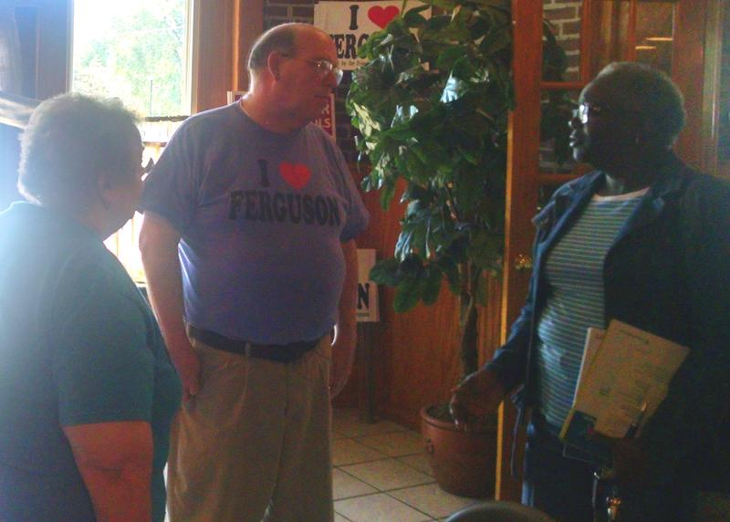 "Committee chairman and former mayor Brian Fletcher talks with a resident and a volunteer about the ""I Love Ferguson"" new store that will sell items including the logo-bearing T-shirts."