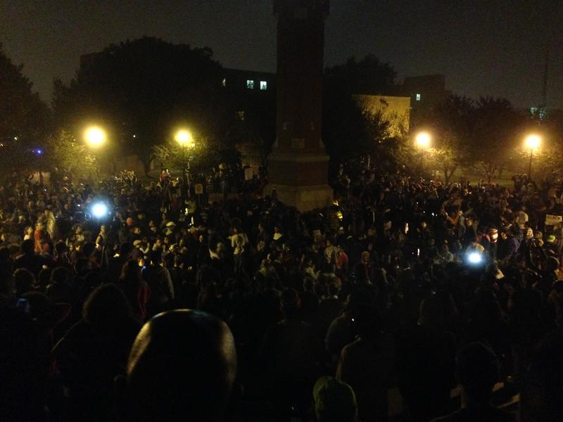 A large crowd gathers at the clocktower on the campus of Saint Louis University.