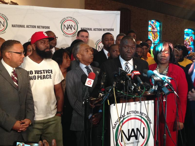 (l to r) Michael Brown, Sr. (second from left, in T-shirt), Al Sharpton and Benjamin Crump (at podium)