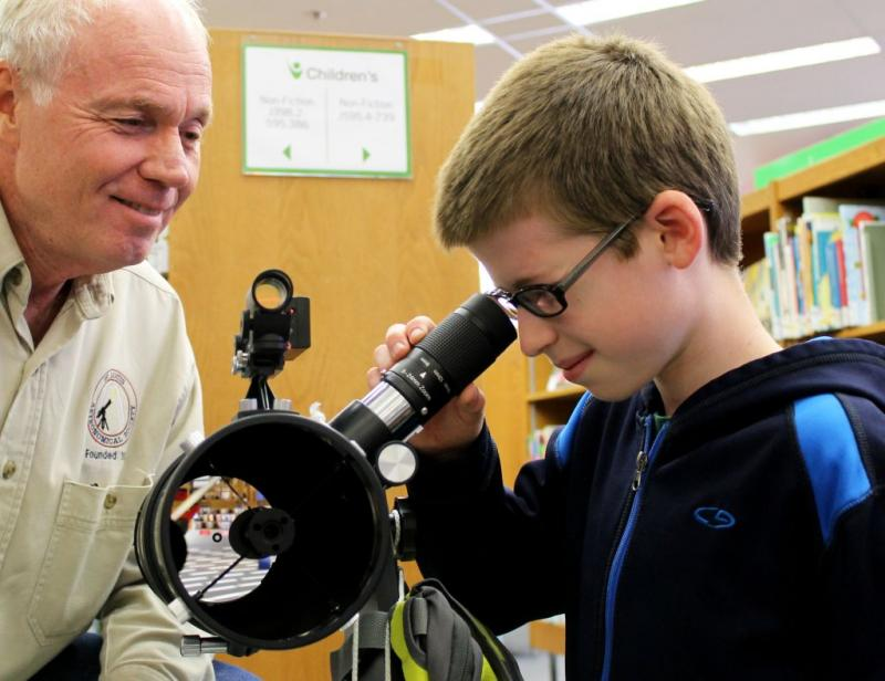 Twelve-year-old Ben Gremaud gets a preview of one of the telescopes at the St. Louis County Library, with the help of the St. Louis Astronomical Society's Don Ficken. If you look closely, you can see the library reflected in the telescope's mirror!