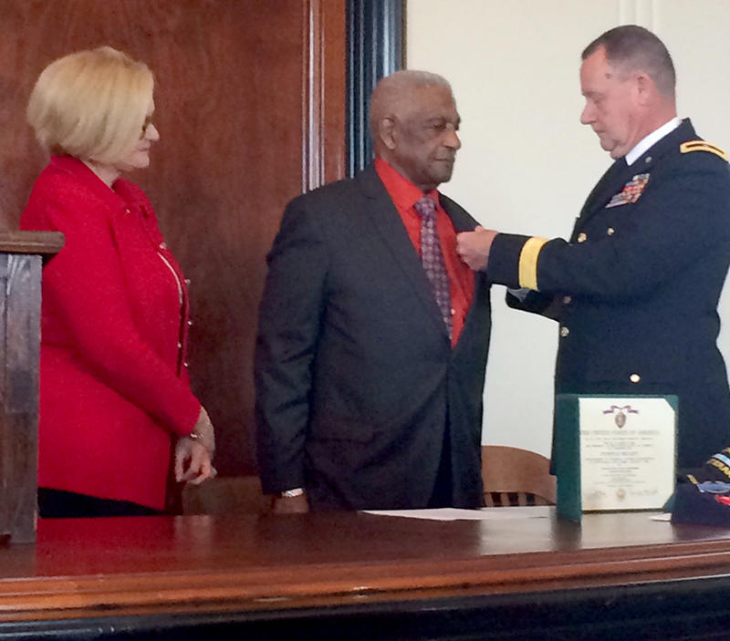 Brigadier General James Robinson, left, pins a medal to Leo Hardin's suit coat as Sen. Claire McCaskill (D-Mo) looks on.