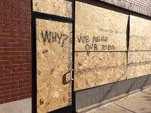 Sign painted on boarded-up window on South Grand