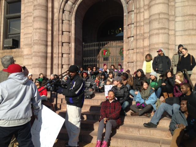 Protesters sit on the steps of St. Louis City Hall, as locked metal grilles bar the doors at a protest on Dec. 17, 2014