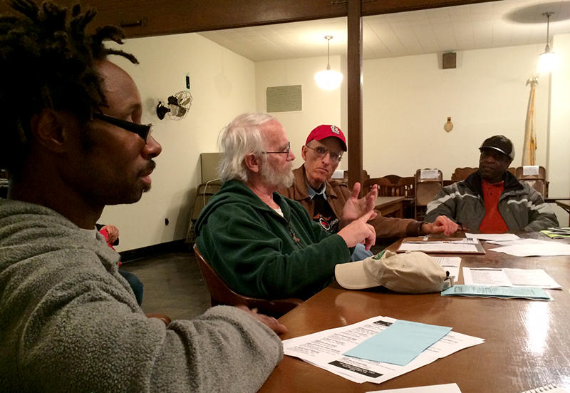 Anthony Knight, left, listens as New Life Shelter Manager Scott Eagen addresses the group. Bob Linsey and Lamont Belle in the backround look on.