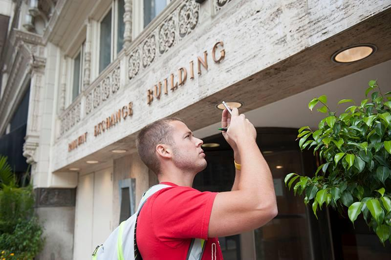 Brett Loehmann, a graduate student in the Sam Fox Design and Visual Arts program at Washington University, photographs the Railway Exchange Building on Sept. 17, 2014.