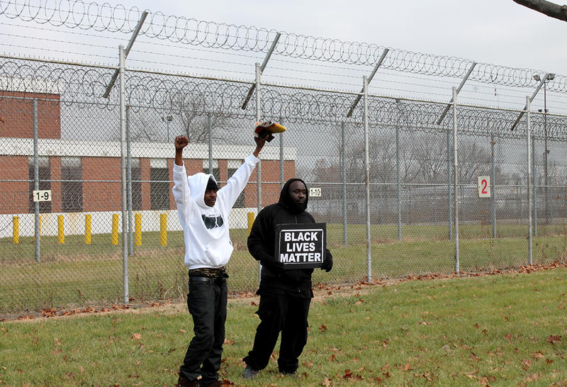 Two men broke from the group and were the first to approach the jail's fence.