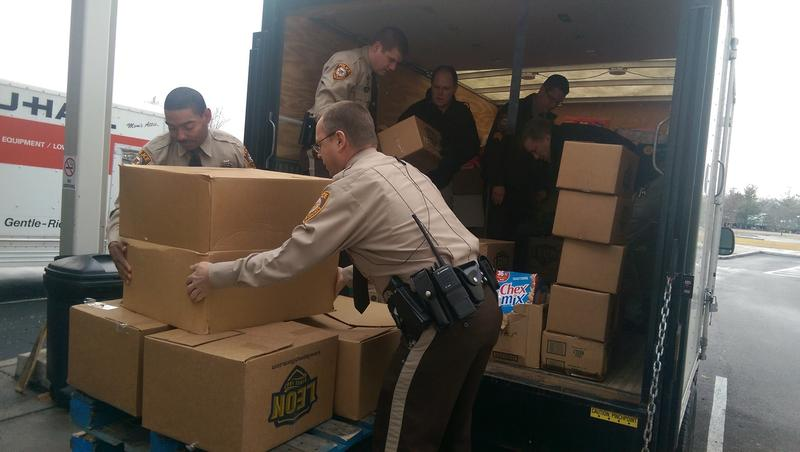 St. Louis County Police officers unload a truck of food donations at the St. Louis Area Foodbank on Monday.