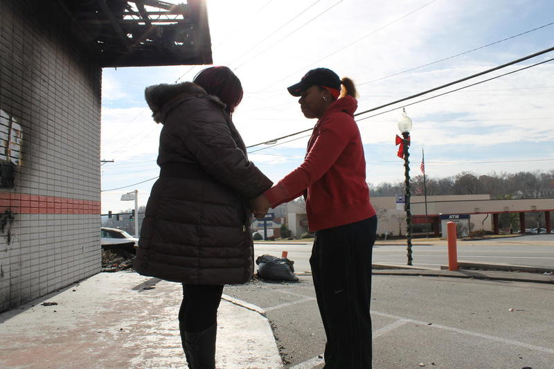 Jeniece Andrews, left, prays with a woman who pulled over her car to embrace her by the rubble of her business, Hidden Treasures. Andrews sank her life savings into her store, which was burned down after a grand jury decided not to indict former Ferguson