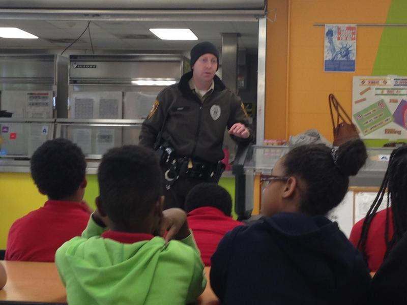 Students who participate in an after -school program at Hanrahan elementary speak with a St. Louis County Police officer.