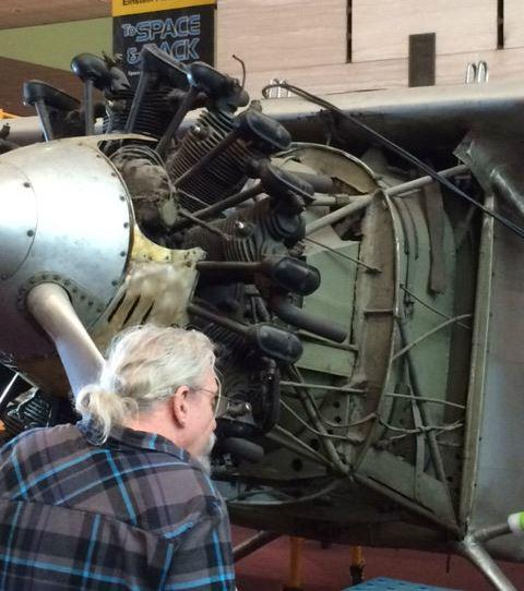 Contractor Karl Heinzel examining engine of the Spirit of St. Louis