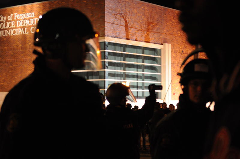 A police officer is silhouetted against Ferguson's police department and municipal court building, during nighttime protests on November 26, 2014.
