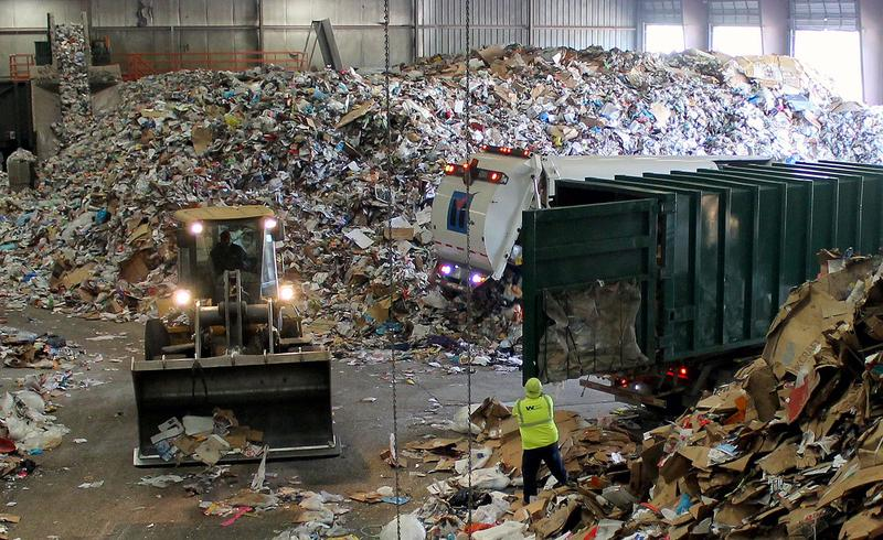 "Trucks dump their loads of single-stream recycling on the ""tip floor"" at Resource Management's Materials Recovery Facility (MRF) in Earth City, Mo."